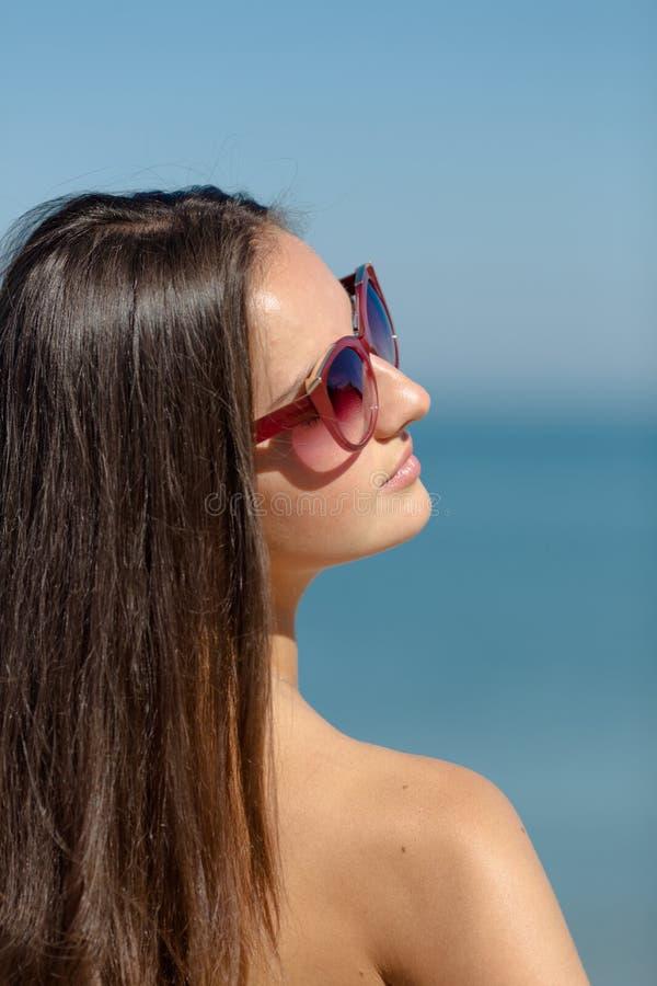 女孩画象太阳镜的在海背景  免版税库存照片