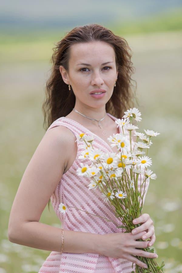 女孩画象有宽松头发的在春黄菊领域 免版税图库摄影