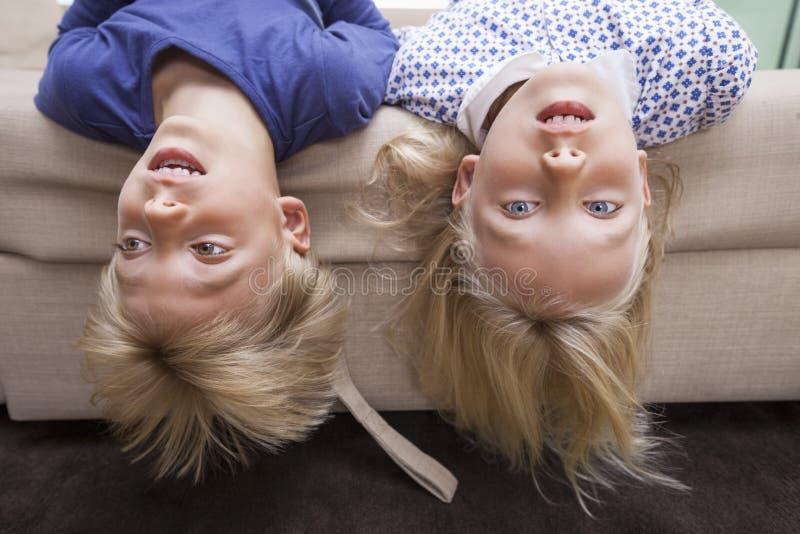 女孩画象有说谎在沙发床上的兄弟的 库存照片