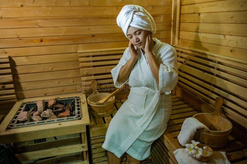 女孩` s在蒸汽浴屋子,刷新在热带木室 保持身体健康 图库摄影