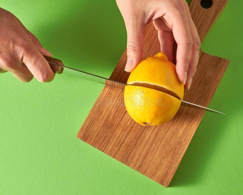 女孩` s手切在一半的一个黄色成熟柠檬在绿色背景的一个木板 在视图之上 库存图片