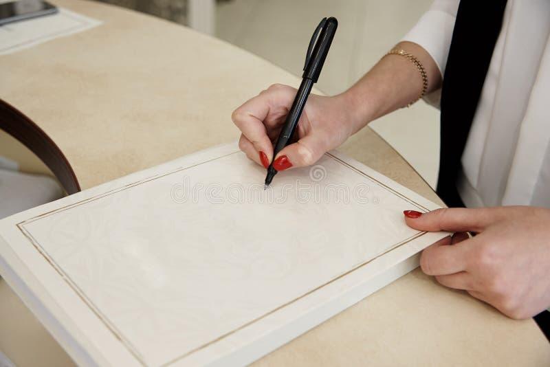 女孩` s手拿着在纸片的一支笔 图库摄影