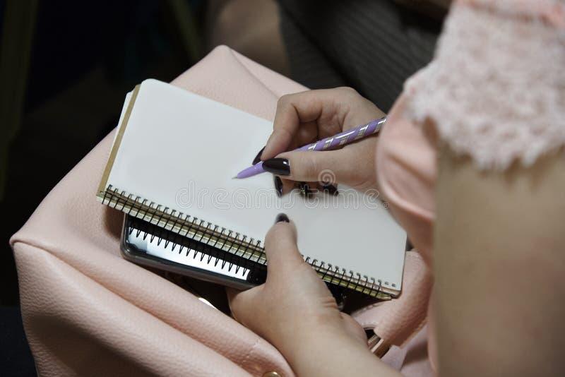 女孩` s手拿着在纸片的一支笔 免版税库存图片