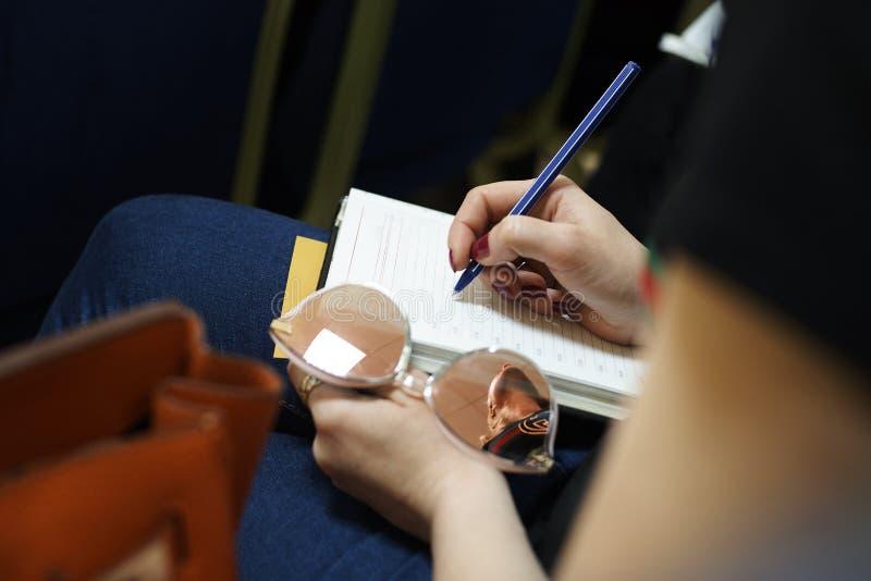 女孩` s手拿着在纸片的一支笔 库存照片