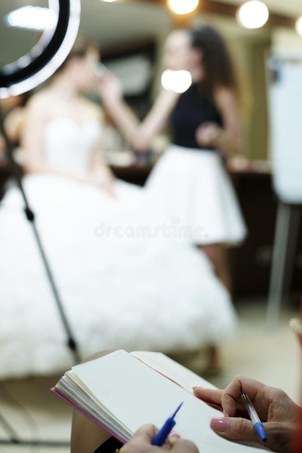 女孩` s手拿着在纸片的一支笔 免版税库存照片
