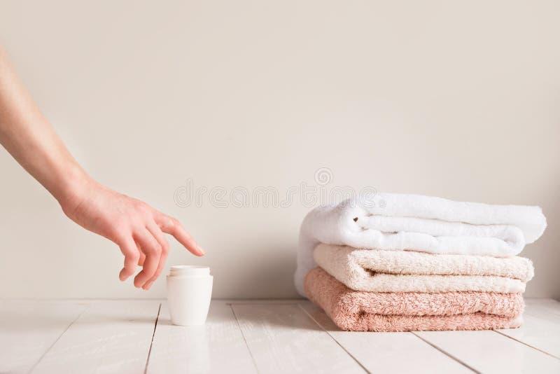 女孩` s特写镜头递到达有化妆奶油的一个瓶子的 秀丽和身体关心在卫生间里 柔软 库存图片