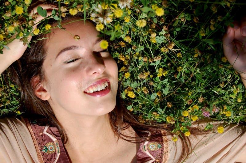 女孩/年轻womanlaying在草微笑 免版税库存照片