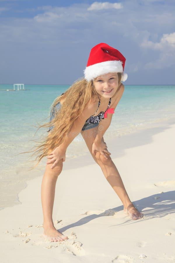 女孩posingon在圣诞老人帽子的海滩 免版税图库摄影