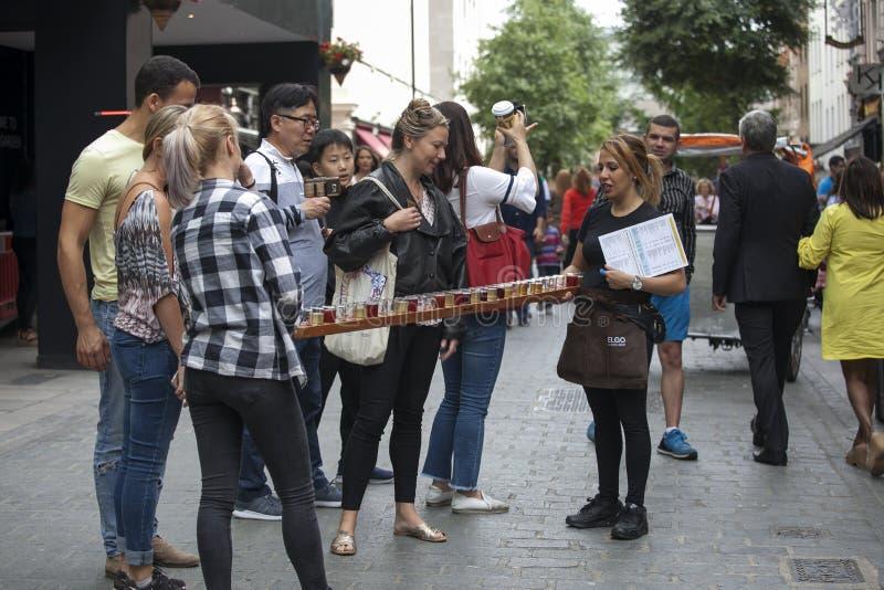 女孩promouters保留杯在一个长的盘子的啤酒 女孩在科文特花园附近给啤酒餐馆做广告 库存图片