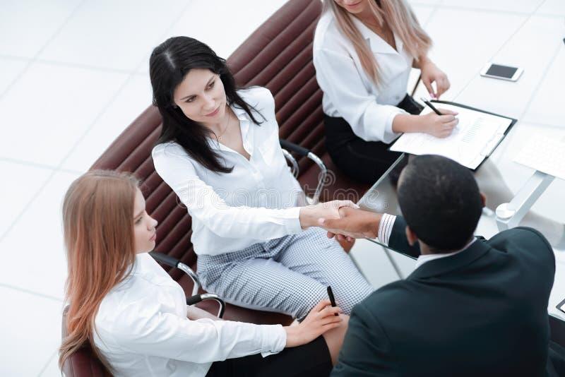 女实业家与伙伴握手在办公室会议上 免版税库存图片
