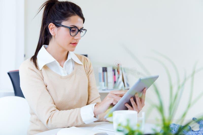 年轻女实业家与数字式片剂一起使用在她的办公室 库存照片