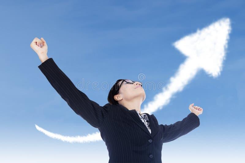 女实业家与箭头标志的自由姿态 免版税库存图片