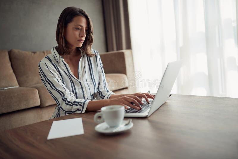 女实业家为从一个家的一台计算机工作有膝上型计算机的a 图库摄影