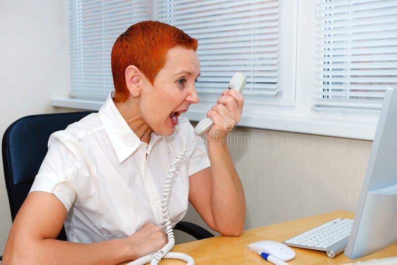 女实业家争论与电话的一个客户 分歧,误解 重音,丑闻 免版税库存图片