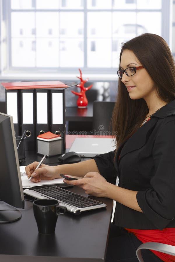 女实业家侧视图书桌的 库存图片