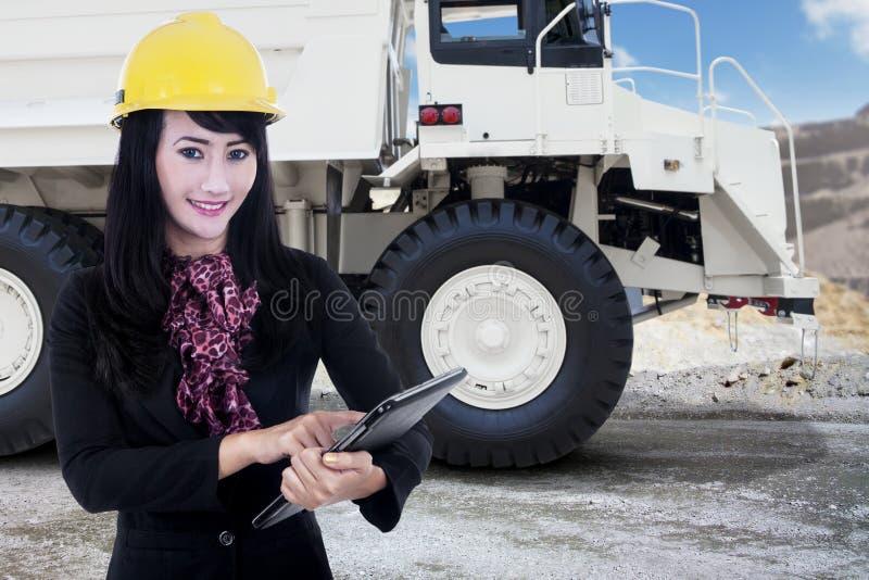女实业家和一个矿用汽车在采矿场所 图库摄影