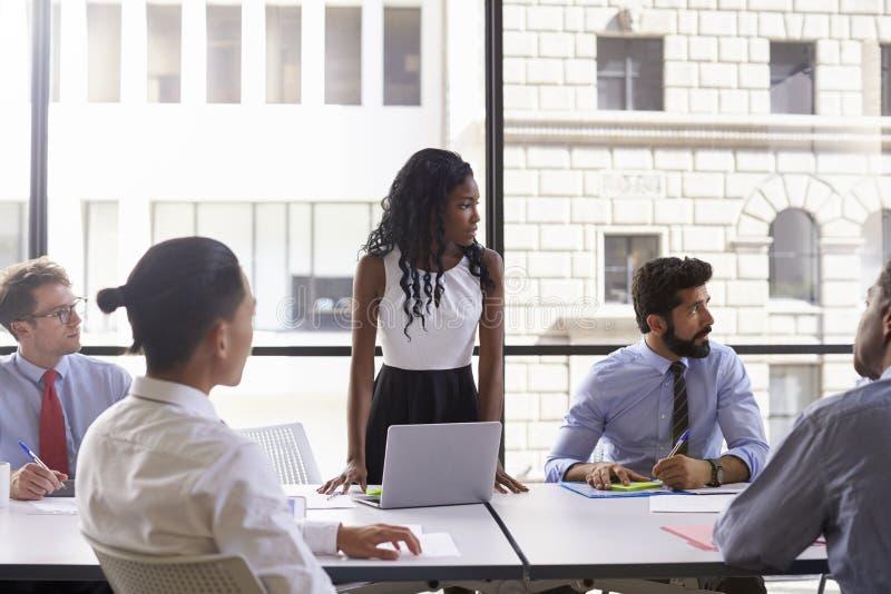 年轻女实业家和同事在会议上,看  免版税库存照片