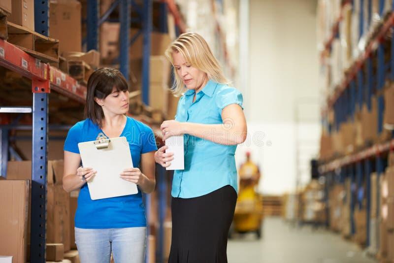 女实业家和女工在配给物仓库里 库存照片