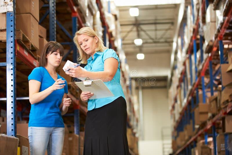 女实业家和女工在配给物仓库里 库存图片