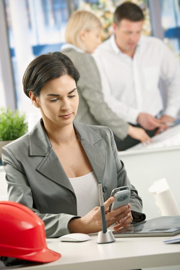 女实业家在使用smartphone的办公室 库存图片