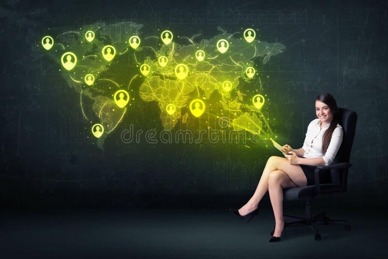 女实业家在有片剂和社会网络世界地图的办公室 库存图片