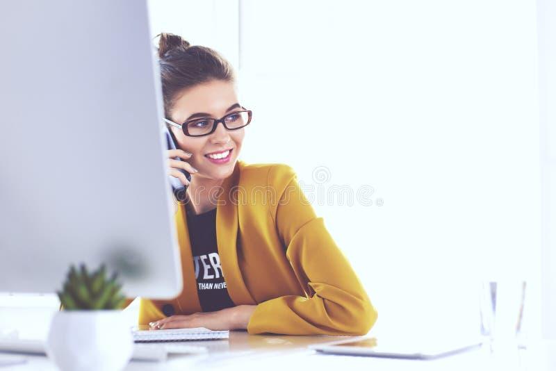 女实业家在有膝上型计算机的办公室坐电话 库存照片