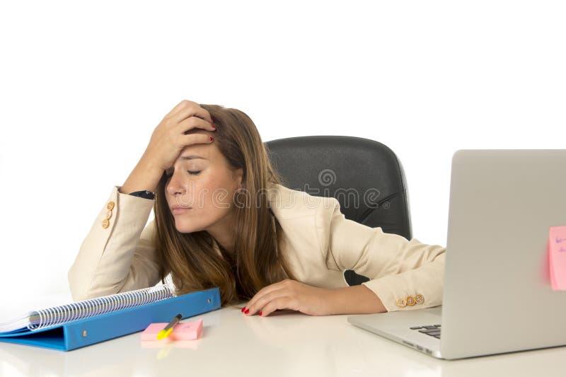 女实业家在被淹没办公计算机的书桌的痛苦重音看起来担心沮丧和 图库摄影