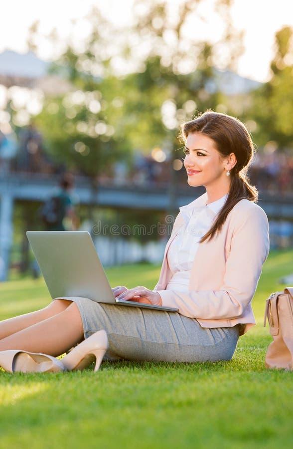 女实业家在运作的公园坐膝上型计算机,晴朗的夏天da 库存图片
