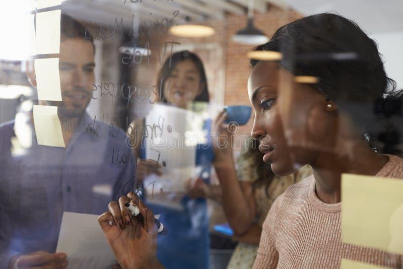 女实业家在玻璃屏幕上的文字想法在会议期间 库存照片