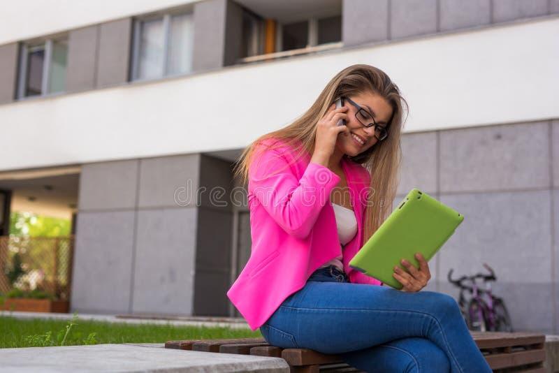 年轻女实业家坐与片剂和smartphon的一条长凳 免版税库存图片