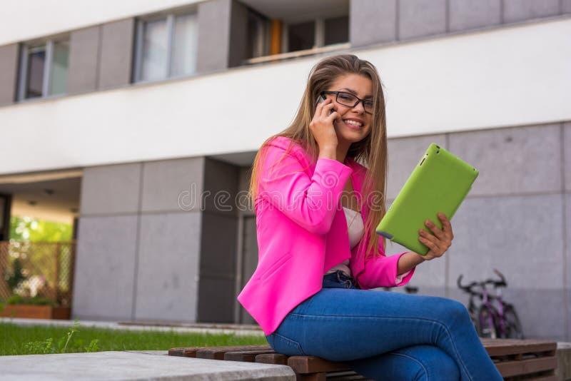 年轻女实业家坐与片剂和smartphon的一条长凳 免版税图库摄影