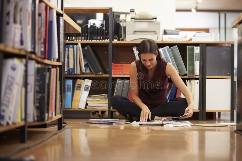 女实业家坐办公室地板读书文件 图库摄影