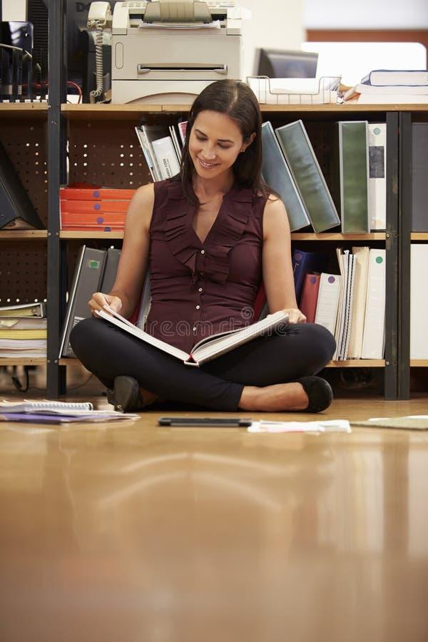 女实业家坐办公室地板读书文件 免版税库存图片