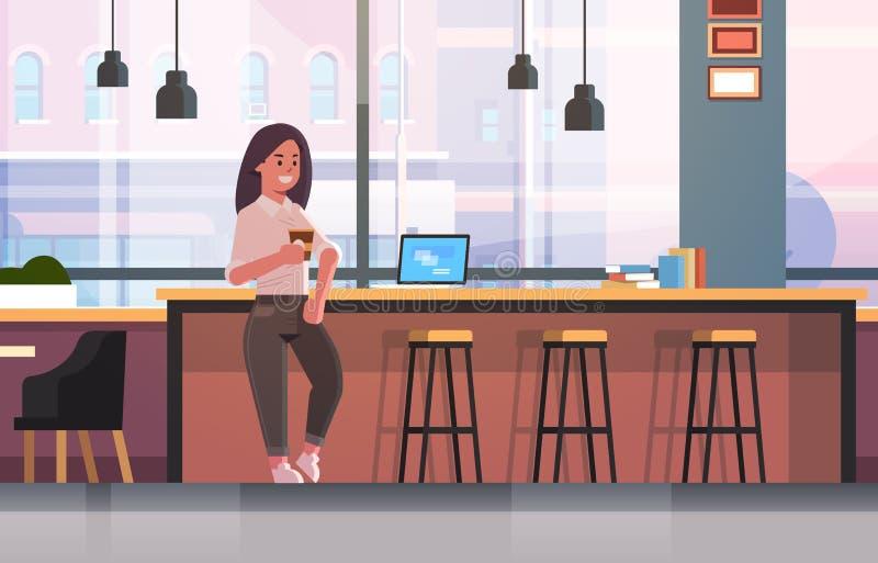 女实业家坐椅子在与现代膝上型计算机咖啡休息概念女商人饮用的热奶咖啡的酒吧柜台 皇族释放例证