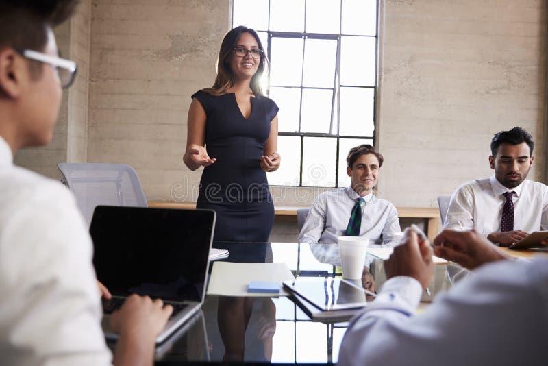 女实业家对同事在会议上,关闭演讲  库存照片