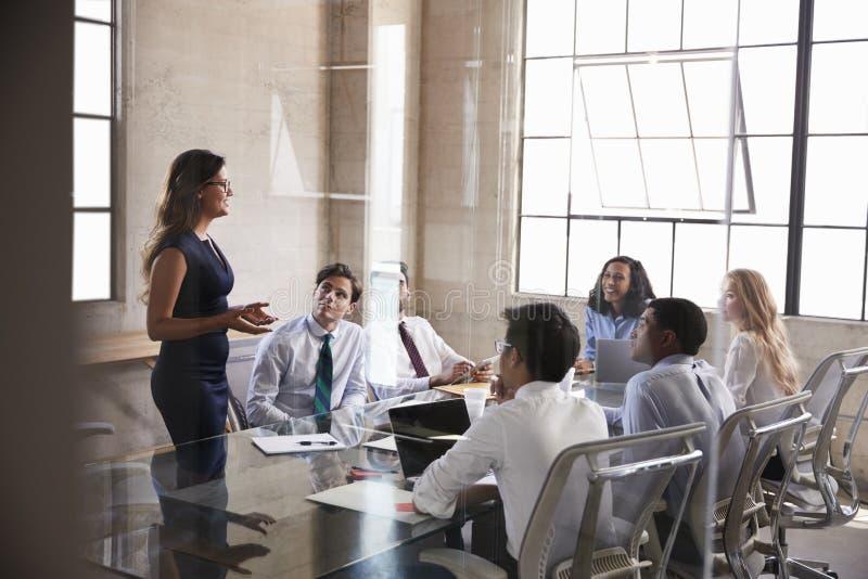 女实业家对同事演讲在会议,侧视图上 免版税库存图片