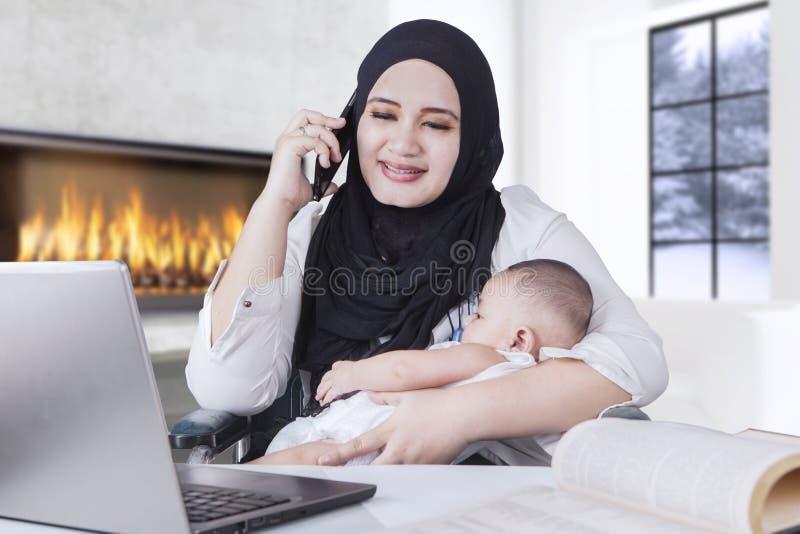 女实业家工作,当抱着她的婴孩时 库存图片