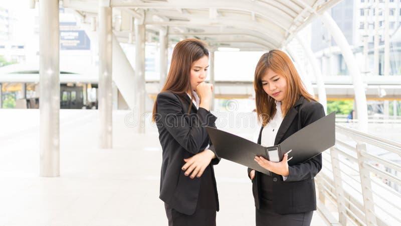 女实业家待办卷宗和互相谈话关于工作 免版税库存照片