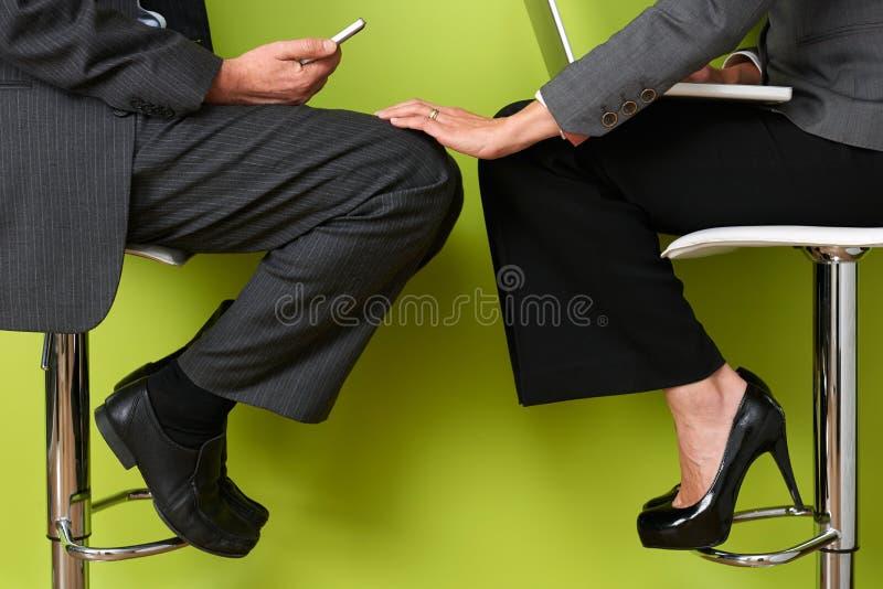女实业家感人的同事的腿 免版税库存图片