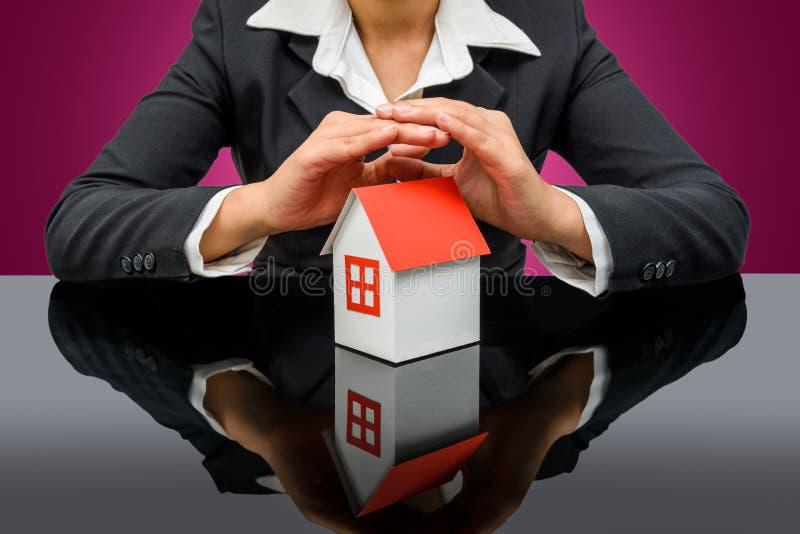 女实业家或房地产经纪商和拿着一个式样房子 库存图片