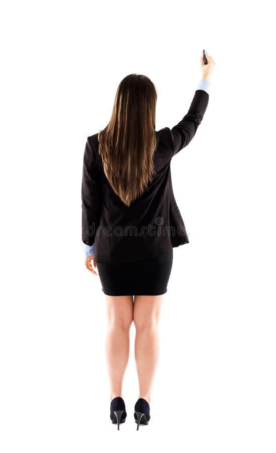 女实业家或老师文字后面看法在白色墙壁上的 免版税库存图片
