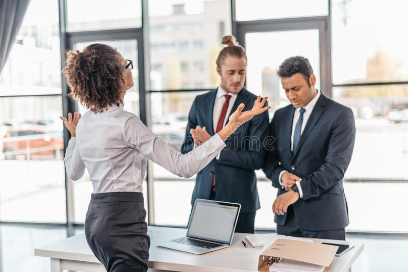 年轻女实业家打手势和争论与工友在办公室 免版税库存图片