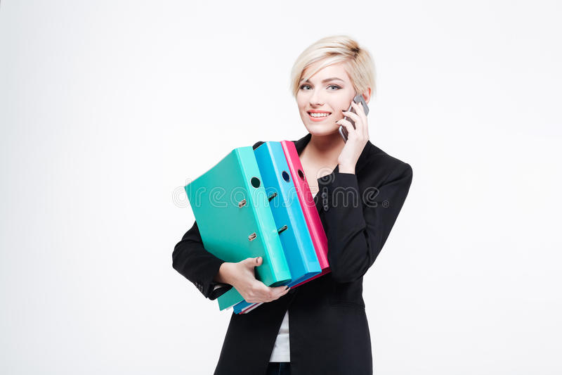 女实业家拿着文件夹和谈话在电话 库存图片