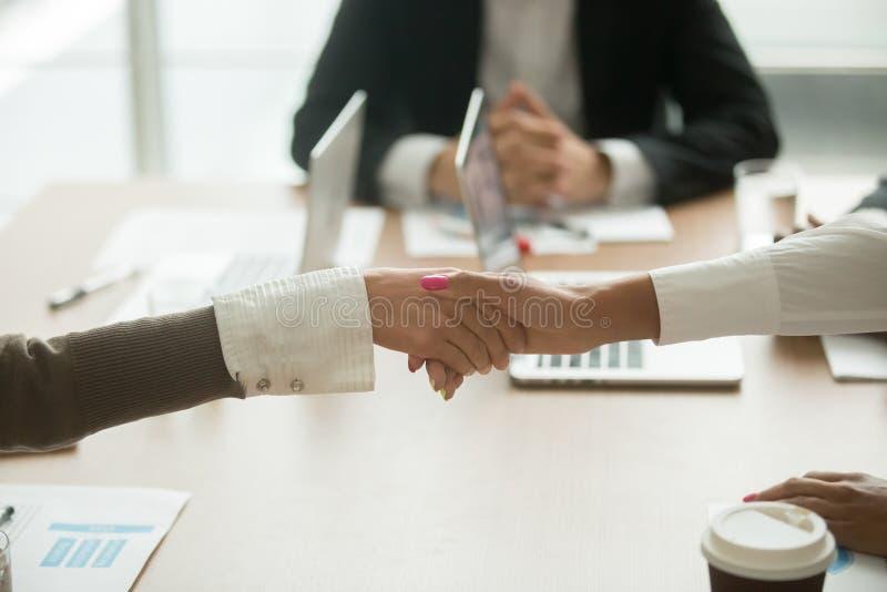 女实业家握手在小组会议,在busin的妇女力量上 免版税库存照片