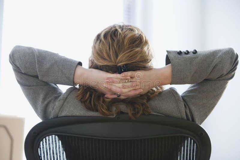 女实业家放松椅子的办公室 免版税库存照片