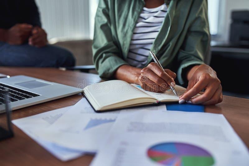 女实业家文字笔记的特写镜头在日志的在办公桌上 免版税库存图片