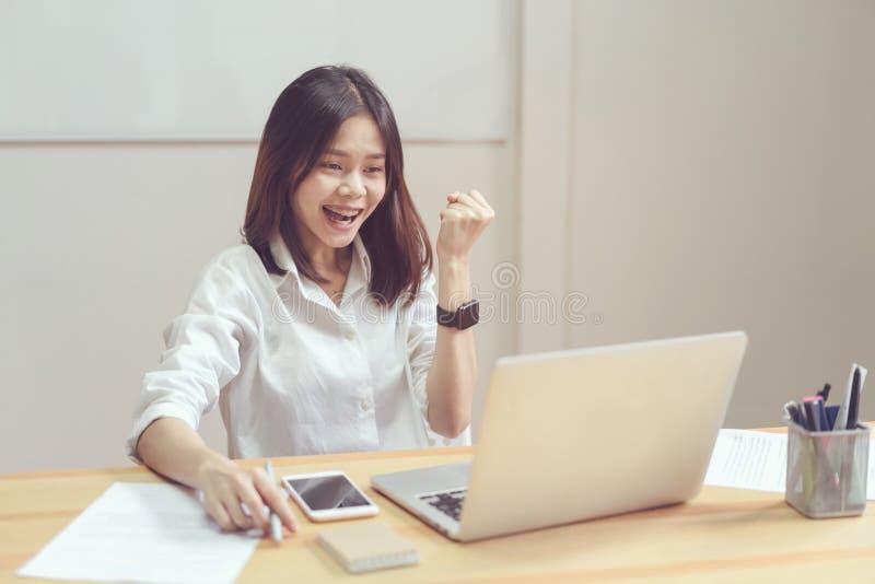 女实业家是愉快在工作成功,并且显示在桌上的文件在offiec 库存图片