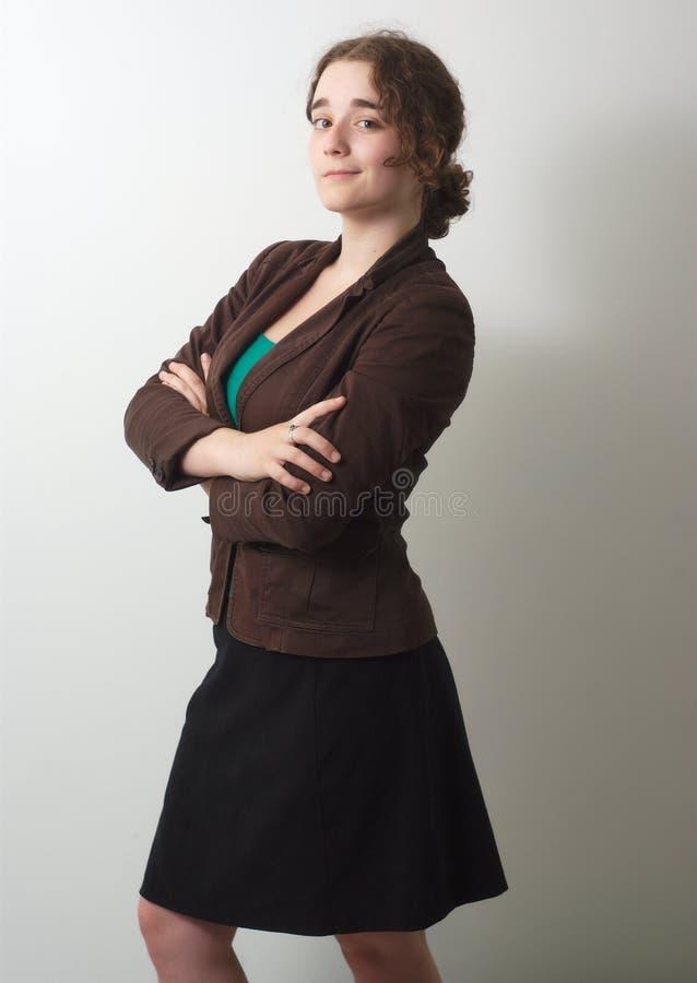 年轻女实业家横渡了在全长灰色的背景的胳膊 库存照片