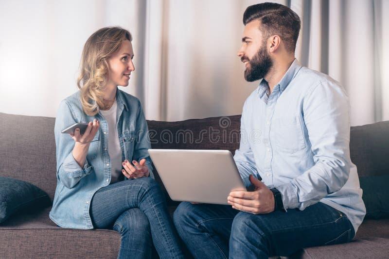 年轻女实业家正面图坐长沙发在屋子里和谈话与坐在她前面的商人 库存照片