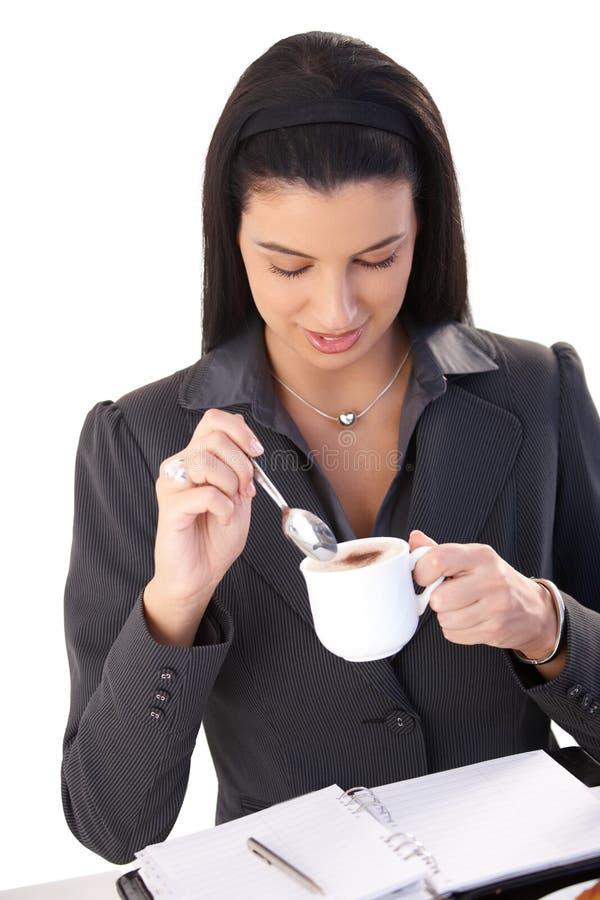 女实业家热奶咖啡享用 免版税库存图片
